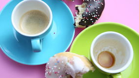 Rotating pink plate with two cups of coffee and donuts. A rotating pink plate with two cups of coffee and donuts stock footage
