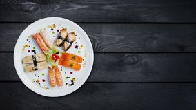 Rotating sashimi set on a white round plate, decorated with small flowers, Japanese food, top view. Black wooden stock footage