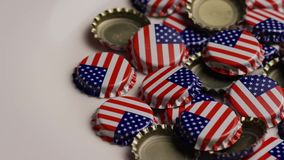 Rotating shot of bottle caps with the American flag printed on them stock footage