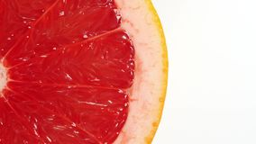Rotating slice of grapefruit. Seamless loopable isolated on white background stock footage