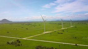 Rotating Slowly Wind Turbines Row in Green Valley. Upper panorama rotating slowly wind turbines row in green valley against blue sky with clouds stock video footage
