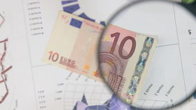 Rotating ten euros and increase with a magnifying glass.