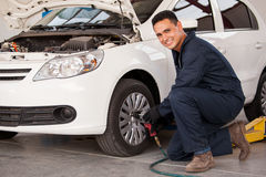 Rotating tires at an auto shop. Handsome young man using an air gun to change a tire at an auto shop Stock Photos
