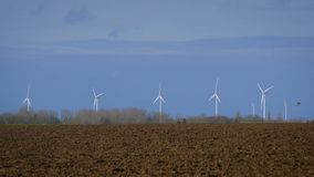 Rotating turbine towers on windmill field on blue sky background. Rotating turbine towers on windmill field. Clean and Renewable Wind Power Farm in Action. Green stock video