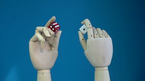 Rotating two wooden manikin hands with lucky dices stock video footage