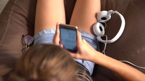 Rotating view of a young woman seated in a chair. Rotating view of a young woman seated in an armchair using her mobile phone to listen to music on stereo stock footage