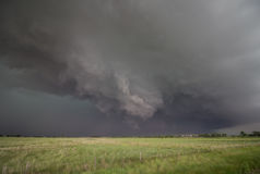 A rotating wall cloud hangs ominously under the base of a supercell thunderstorm. Stock Images