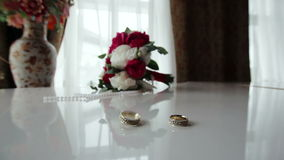 Rotating wedding rings near bouquet on the piano stock footage
