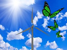 Rotating wind turbine and green butterflies Stock Photos