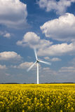 Rotating Wind Turbine under a blue, cloud-strewn sky Stock Photography