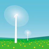 Rotating wind turbines and blue sky. Rotating wind turbines among green grass and flowers against the blue sky background Stock Image