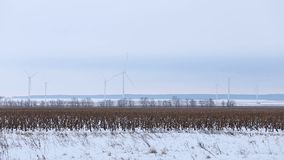 Rotating wind turbines in the distance in a snowy field stock footage