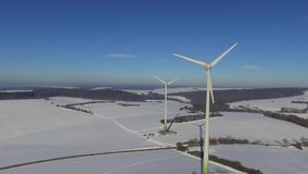 Rotating Wind Wheels in snow-covered winter scenery in Germany. Two rotating wind wheels turbines in snow-covered winter landscape in the taunus mountains in stock footage