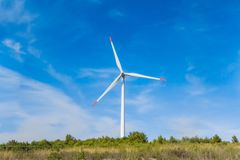 Rotating windmill generating renewable energy wind power at land. Sustainability by windmills turbines preventing climate change with regenerative clean green stock image