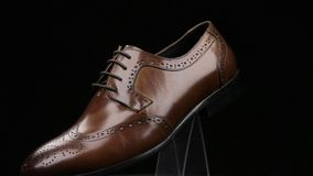 Rotation and approximation of brown classic men`s shoes on a black background. Copy space. Fashion background stock video