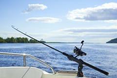 Rotation avec la pêche à la traîne sur la coque du ` s de bateau sur le fond Photo stock