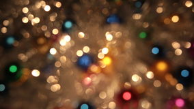 Rotation bokeh from golden tinsel and colorful balls. Christmas and new year background. Celebration, golden light on golden backdrop stock footage
