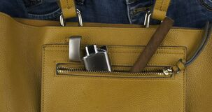 Rotation of a cigar and a lighter protruding from a pocket of a female bag. Bad habits concept.