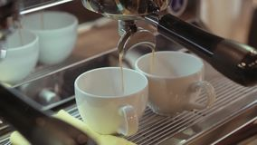 Rotation, close up view of a silver coffee machine pouring hot, fresh coffee in two white cups. An espresso machine stock video