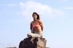 Rotation colourful. Beautiful girl performing a rotational yoga asana on the rocks near Sozopol,Bulgaria Stock Images