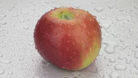 Rotation, drops of water fall on a ripe red apple. stock video