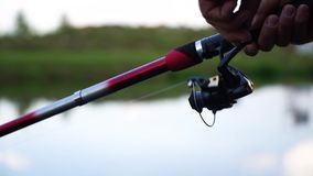 Close up rotation of the handle with a reel of fishing rod with lake on background. A man fishing on a big lake tightens stock video footage