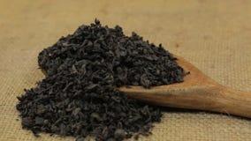 Rotation, Haufen des schwarzen Tees der trockenen Blätter, der von einem hölzernen Löffel auf Leinwand fällt stock video footage