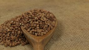 Rotation, heaps of buckwheat grains, falling from a wooden spoon on burlap. Food stock footage