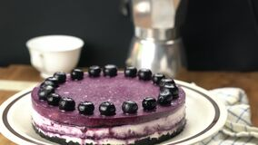 Rotation of homemade blueberry cheesecake in brown ceramic dish.