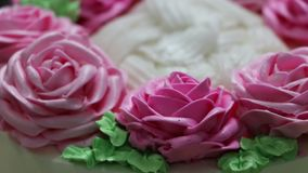 The rotation of the pink roses and green leaf of butter cream on the white cake. stock footage