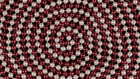 Rotation of a spiral made of red and white beads on a black background. View from above stock footage