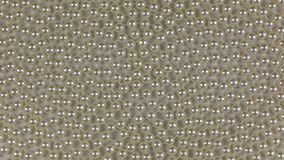 Rotation of a spiral of white beads lying on a white cloth. View from above stock video