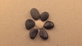Rotation of the stones in the shape of a flower lying on the sand. Concept. View from above stock footage