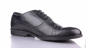 Rotation of a stylish classic black shoe with laces on a white background. Classic men`s fashion stock video footage