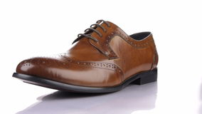 Rotation of a stylish classic brown shoe with laces on a white background. Classic men`s fashion stock video footage