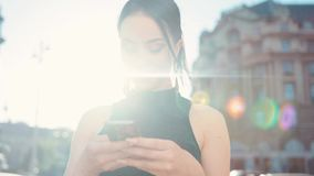 Rotation view of a beautiful brunette using her phone, happily smiling to the screen, actively texting back in a bright