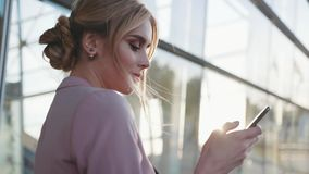Rotation view of an elegant blonde business lady using her phone, looking around in a bright sunshine. Modern