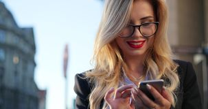 Rotation view of a gorgeous blonde woman in a formal wear and glasses standing outside the office and using her phone