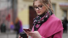 Rotation view of a stylish lady holding coffee-to-go and texting. Modern lifestyle. Trendy look. stock footage