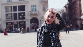 Rotation view of a young attractive blonde girl with red lipsticks, and casual leather jacket having a walk in the stock video