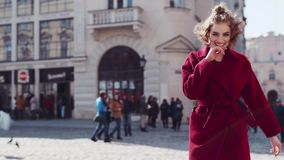 Rotation view of a young attractive woman in a red coat having fun, laughing, jumping in the city center. Stylish look stock footage