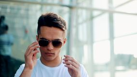 Rotation view of young man standing by the airport terminal takes off the sunglasses. Male style, waiting for the stock footage