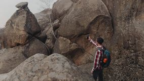 Rotation view of a young stylish man in a checkered shirt, with a backpack taking selfie surrounded with a high rocks stock footage