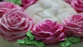 Rotationen av de rosa rosorna och det gröna bladet av smörkräm på den vita kakan arkivfilmer