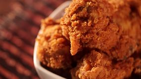 Rotations-Eimer voll des knusperigen gebratenen Huhns mit Rauche auf braunem Hintergrund stock footage