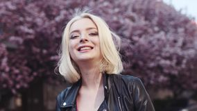 Rotationssikt av den blåögda blonda kvinnan som tycker om det soliga vädret för vår och körsbärsröd blomning i centret arkivfilmer