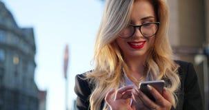 Rotationssikt av en ursnygg blond kvinna i formella kläder och exponeringsglas som står utanför kontoret och använder hennes tele