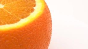 Rotazione arancio cutted della mezza struttura sulla piattaforma girevole Isolato su bianco Chiuda sulla macro video d archivio