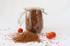 Rotbrauner Reis, Kirschtomaten, weißer Hintergrund lizenzfreies stockbild