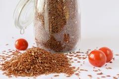 Rotbrauner Reis, Kirschtomaten, weißer Hintergrund lizenzfreies stockfoto